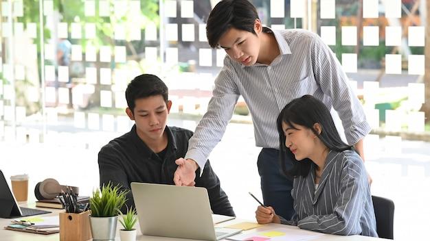 Jonge team start commerciële vergadering met laptopcomputer op lijst.