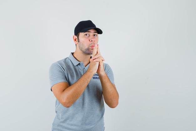 Jonge technicus blaast op vingerpistool in grijs uniform en kijkt zelfverzekerd.