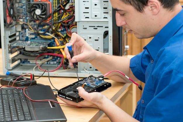 Jonge technicus die aan gebroken computer in zijn bureau werkt