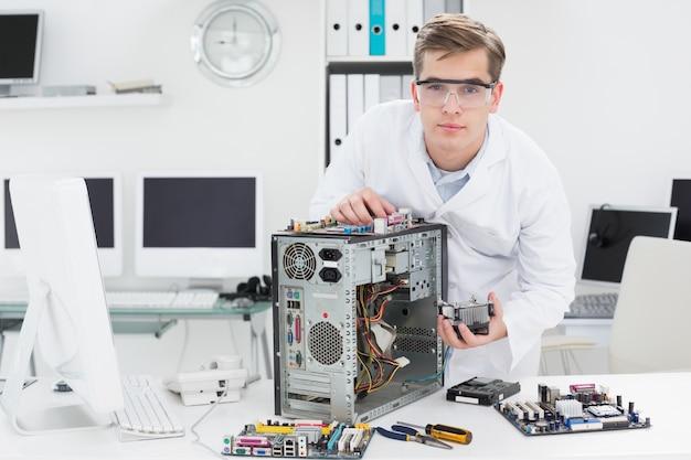 Jonge technicus die aan gebroken computer werkt
