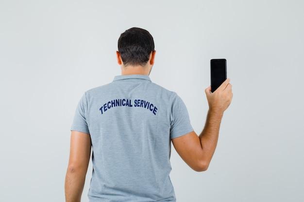 Jonge technicus die achteruit draait en zijn telefoon in grijs uniform toont en er elegant uitziet.