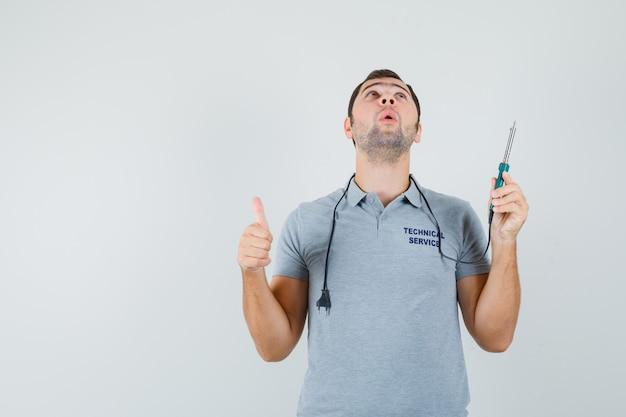 Jonge technicus die boor in één hand houdt terwijl hij zijn duim toont en omhoog kijkt in grijs uniform en verbaasd kijkt.