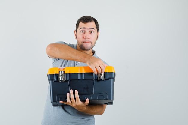 Jonge technicus die de gereedschapskist in grijs uniform probeert te openen en optimistisch kijkt.