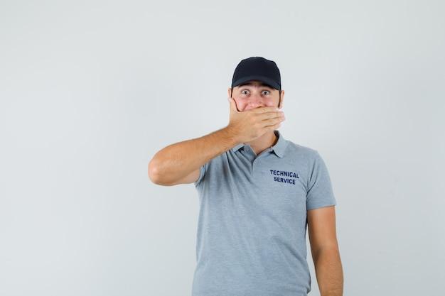 Jonge technicus die hand op mond in grijs uniform houdt en opgewonden kijkt.