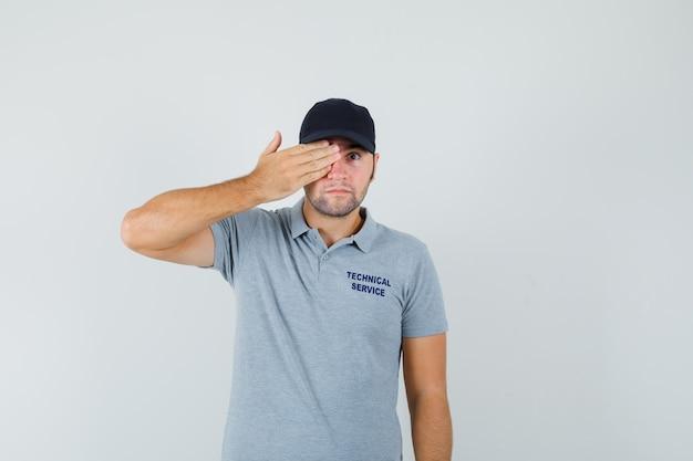 Jonge technicus die in grijs uniform hand op oog houdt en kalm kijkt.