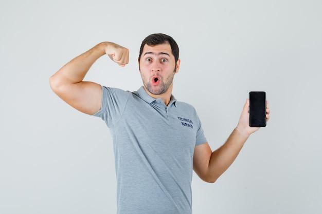 Jonge technicus die in grijs uniform mobiele telefoon houdt, spieren toont en zelfverzekerd kijkt, vooraanzicht.