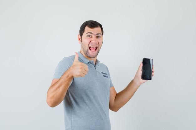 Jonge technicus die mobiele telefoon houdt, duim in grijs uniform toont en zalig, vooraanzicht kijkt.