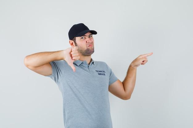 Jonge technicus die opzij wijst, duim in grijs uniform toont en somber kijkt.