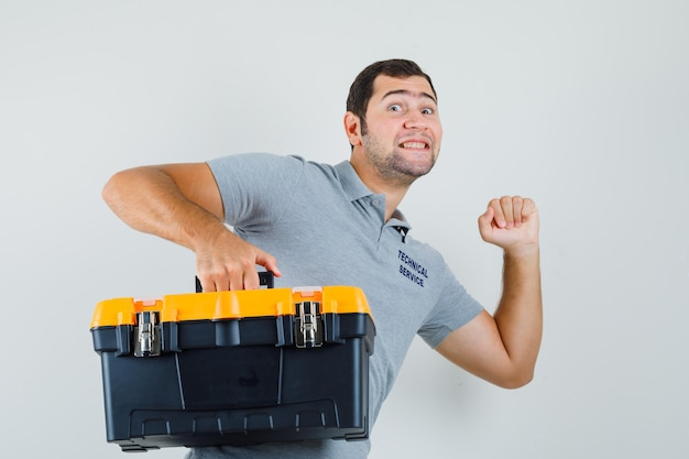 Jonge technicus die toolbox draagt en in grijs uniform probeert te rennen en optimistisch kijkt.