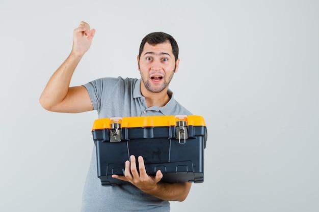 Jonge technicus die toolbox houdt terwijl hij zijn ene hand in grijs uniform opheft en verbaasd kijkt.