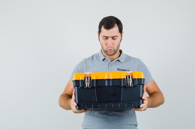 Jonge technicus die toolbox in grijs uniform bekijkt en verbaasd kijkt.