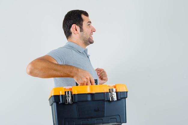 Jonge technicus die toolbox in grijs uniform draagt en optimistisch kijkt.