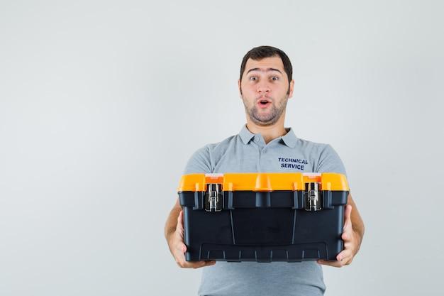 Jonge technicus die toolbox in grijs uniform voorstelt en verbaasd kijkt.