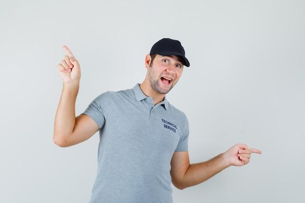 Jonge technicus die vingers op en neer in grijs uniform richt en vrolijk kijkt.