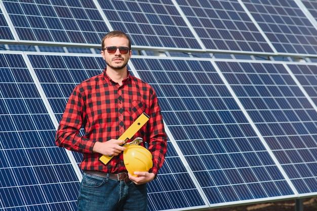 Jonge technicus die zonnepanelen op fabrieksdak installeert