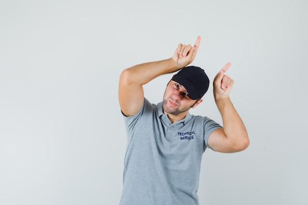 Jonge technicus houdt vingers boven het hoofd als stierhoorns in grijs uniform en ziet er grappig uit.