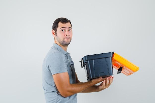 Jonge technicus in grijs uniform bedrijf geopende toolbox en op zoek ernstig.