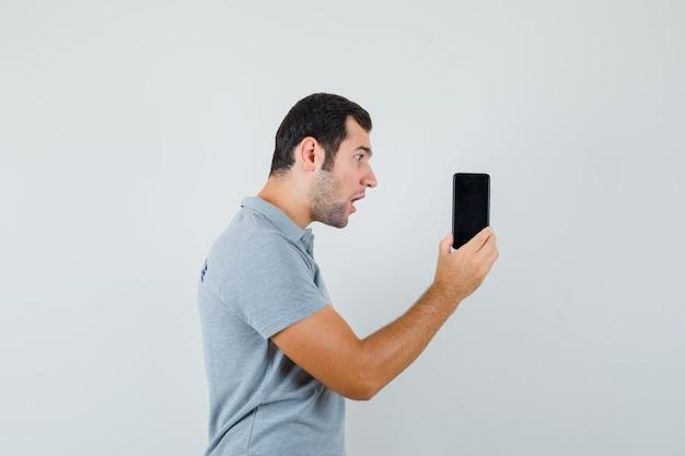 Jonge technicus in grijs uniform bekijkt zijn telefoon verbazingwekkend terwijl hij hem vasthoudt en verbaasd kijkt.