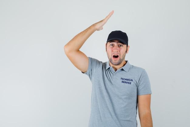 Jonge technicus in grijs uniform die hand boven het hoofd houdt en verbaasd kijkt door het nieuws.