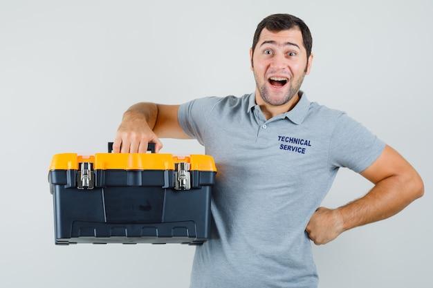 Jonge technicus in grijs uniform die toolbox opheft terwijl hij zijn hand op de taille houdt en verbaasd kijkt.