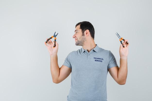 Jonge technicus in grijs uniform kijken naar de tang die in beide handen houdt en optimistisch, vooraanzicht kijkt.