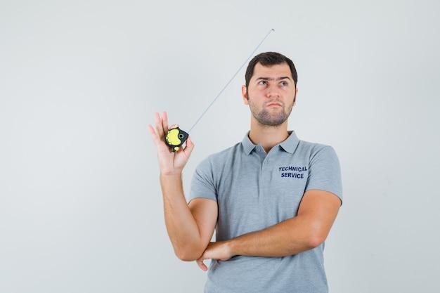 Jonge technicus in grijs uniform meetlint in de ene hand en staande in denken pose en peinzend kijken.