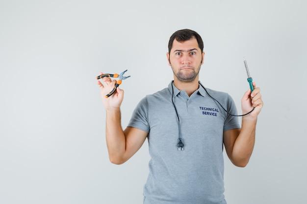 Jonge technicus in grijs uniform met boor in de ene hand, tang in een andere hand en op zoek naar serieus.