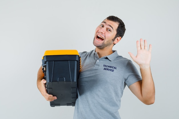 Jonge technicus in grijs uniform met toolbox terwijl iemand begroet en er optimistisch uitziet.