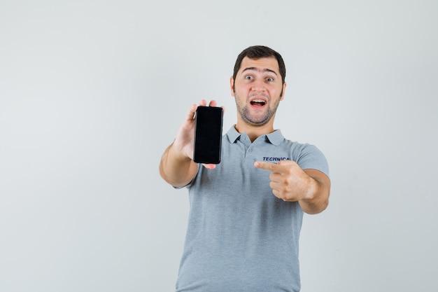 Jonge technicus in grijs uniform wijzend op mobiele telefoon en vrolijk, vooraanzicht kijken.