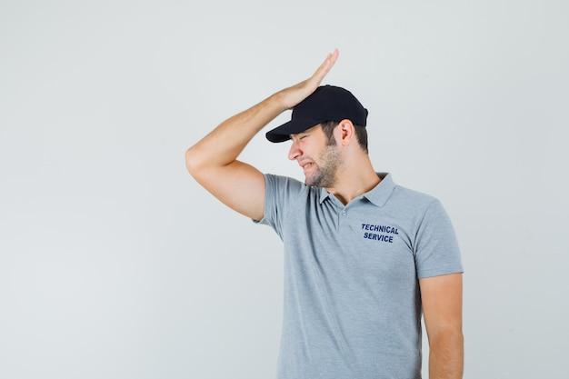 Jonge technicus in grijs uniform zijn hand op het hoofd zetten en verward kijken.