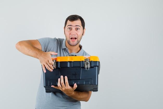 Jonge technicus in grijze uniforme gereedschapskist met zijn beide handen en op zoek geschokt.