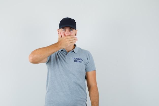 Jonge technicus in grijze uniforme hand op de mond houden en serieus kijken.