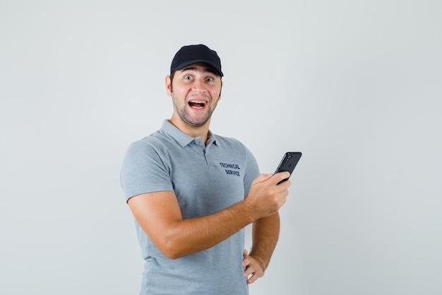 Jonge technicus leest de berichten op zijn telefoon en glimlacht terwijl hij zijn hand op de taille houdt in een grijs uniform en er verbaasd uitziet.