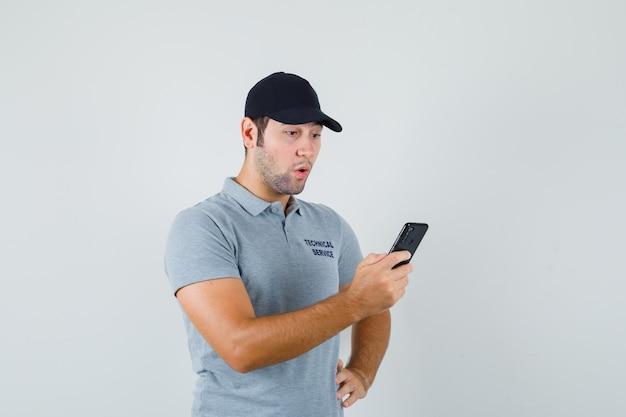 Jonge technicus leest de berichten op zijn telefoon terwijl hij zijn hand op de taille houdt in een grijs uniform en verbaasd kijkt.