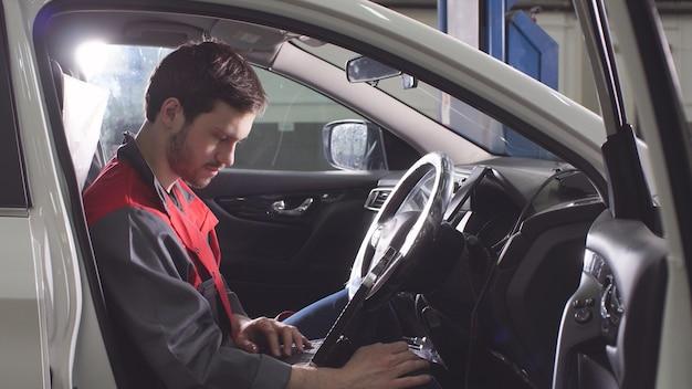 Jonge technicus man making engine service van auto in garage.