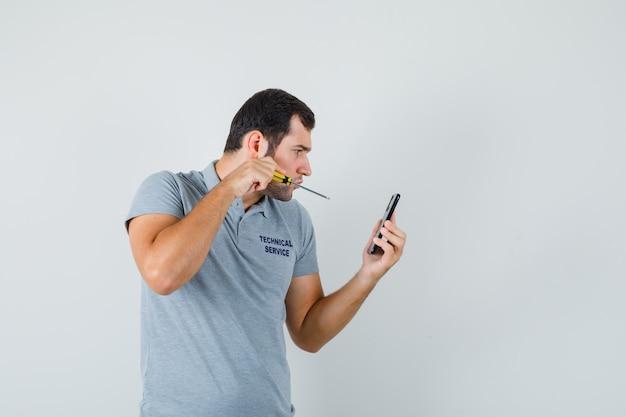 Jonge technicus met schroevendraaier en probeert de achterkant van zijn telefoon in grijs uniform te openen en gefocust op zoek.