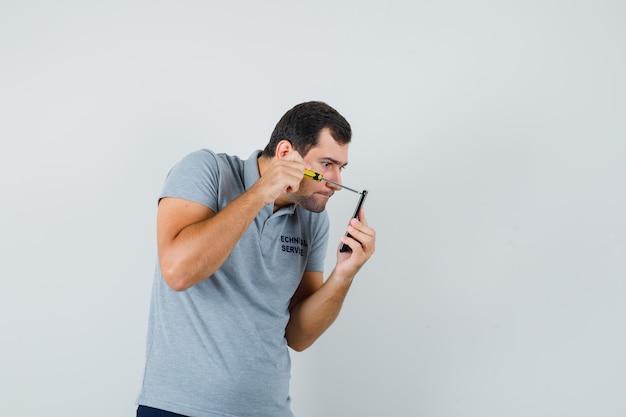 Jonge technicus schroevendraaier vasthouden en de achterkant van zijn telefoon openen in grijs uniform en gefocust op zoek.