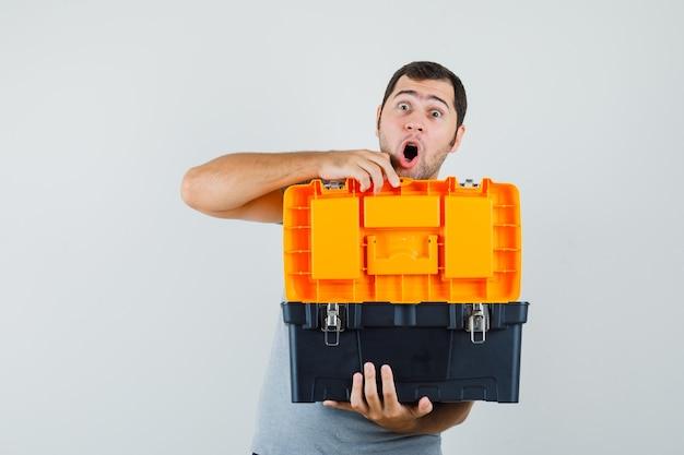 Jonge technicus toolbox openen met zijn beide handen in grijs uniform en versuft op zoek.