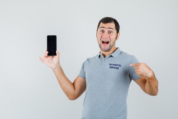 Jonge technicus wijst naar deze telefoon met wijsvingers in grijs uniform en kijkt verbaasd, vooraanzicht.