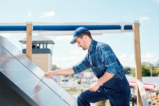 Jonge technicusmeester in werkkleding die over zonnepaneel op het dak buigt terwijl het handvat wordt aangepast