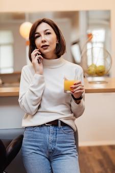 Jonge tedere dame in wit t-shirt en spijkerbroek in de keuken praten aan de telefoon