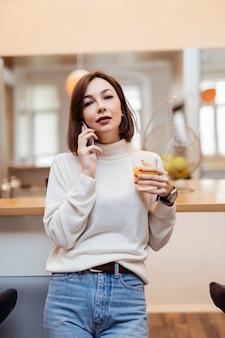 Jonge tedere dame is in de keuken praten aan de telefoon