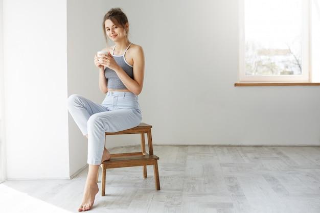Jonge tedere donkerbruine vrouw het glimlachen de zitting van de holdingskop op stoel over witte muur vroeg in ochtend.