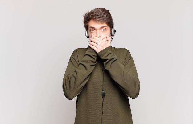 Jonge telemarketeer bedekt mond met handen met een geschokte, verbaasde uitdrukking, houdt een geheim of zegt oeps