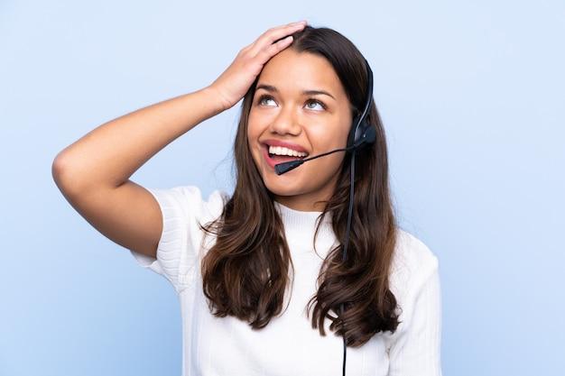 Jonge telemarketeer colombiaanse vrouw over geïsoleerde blauwe muur lachen