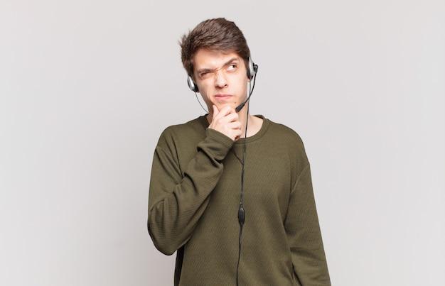Jonge telemarketeer die denkt, zich twijfelachtig en verward voelt, met verschillende opties, zich afvragend welke beslissing hij moet nemen