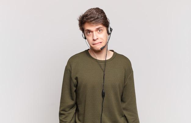 Jonge telemarketeer die verbaasd en verward kijkt, lip bijt met een nerveus gebaar, niet wetend het antwoord op het probleem