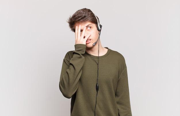 Jonge telemarketeer die zich verveeld, gefrustreerd en slaperig voelt na een vermoeiende, saaie en vervelende taak, gezicht met de hand vasthoudend