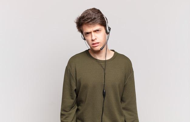 Jonge telemarketeer die zich verward en verward voelt, met een stomme, verbijsterde uitdrukking die naar iets onverwachts kijkt