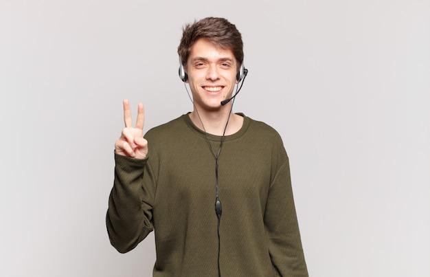 Jonge telemarketeer glimlacht en ziet er vriendelijk uit, toont nummer twee of seconde met hand naar voren, aftellend